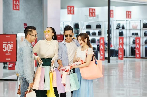 Amici allegri in piedi nel centro commerciale con molte borse della spesa dopo aver acquistato scarpe e vestiti in vendita il venerdì nero