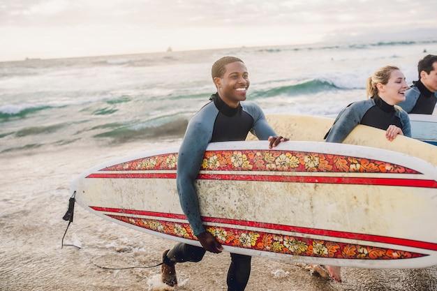 Amici allegri che fanno surf in spiaggia
