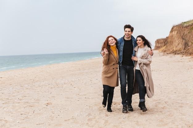 Amici allegri che camminano al mare in autunno