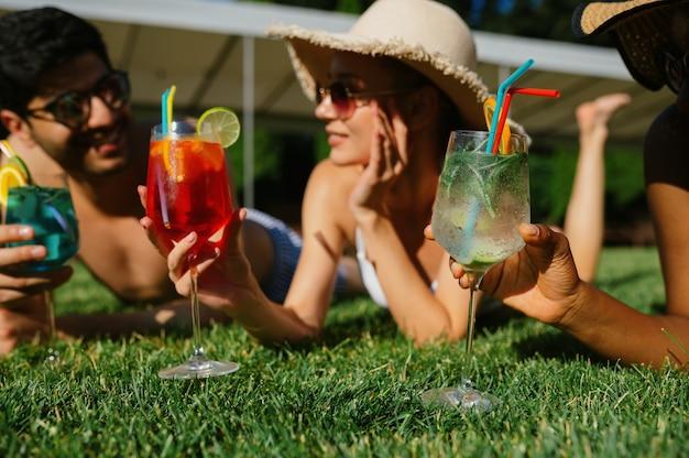 Amici allegri con cocktail riposano sull'erba vicino alla piscina. persone felici che si divertono durante le vacanze estive, feste a bordo piscina all'aperto. un uomo e due donne stanno prendendo il sole