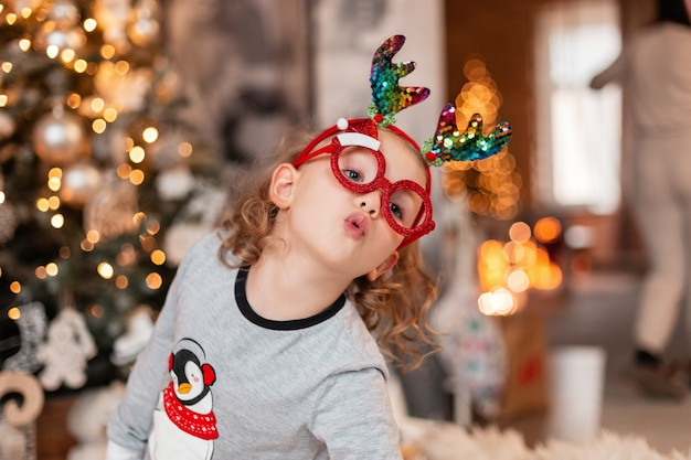 Allegra divertente bella bambina con occhiali da babbo natale giocattolo e corna di cervo di natale in pigiama alla moda sullo sfondo dell'albero di natale e luci