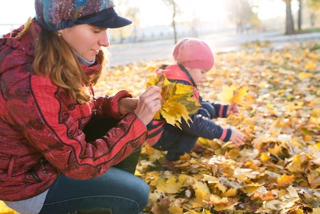 La madre allegra e divertente gioca con le foglie di acero gialle della figlia positiva mentre cammina in un soleggiato parco autunnale. concetto di buone tradizioni familiari