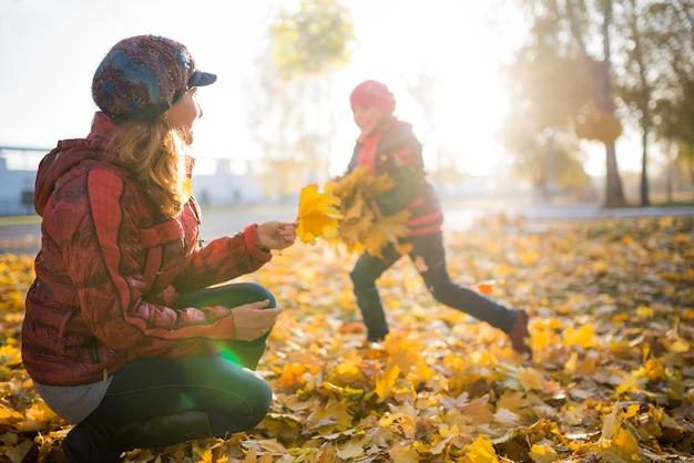 La madre allegra e divertente gioca con le foglie d'acero gialle della figlia positiva mentre cammina in un soleggiato parco autunnale. concetto di buone tradizioni familiari
