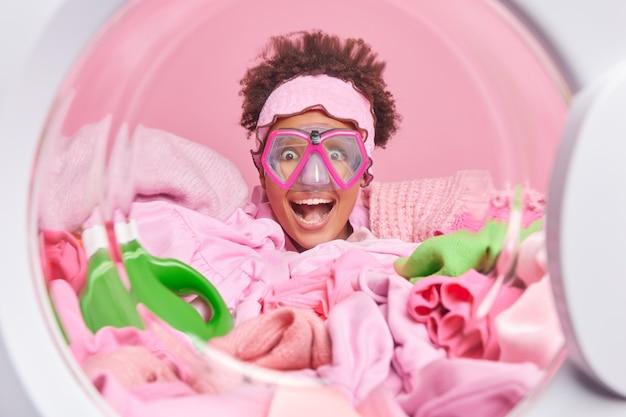 La donna allegra e divertente indossa gli occhiali da snorkeling posa intorno al bucato e la polvere liquida sciocchi intorno alle pose dall'interno della lavatrice fa il lavaggio durante il fine settimana