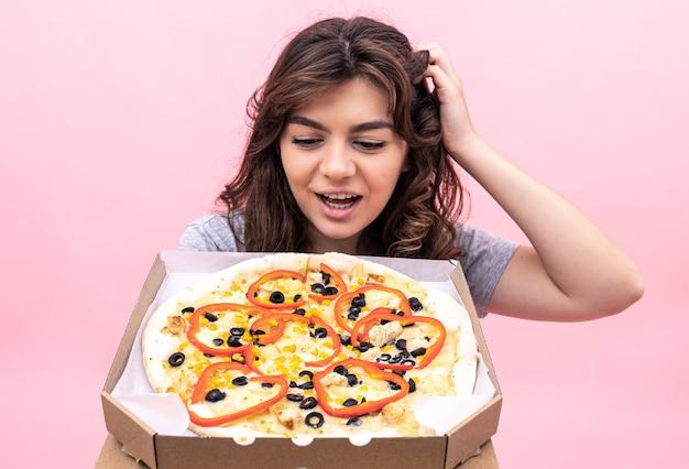 La ragazza allegra guarda in modo appetitoso la pizza appena sfornata in una scatola per la consegna su uno sfondo rosa.