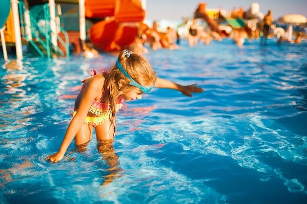 Ragazza allegra in un costume da bagno luminoso e occhiali da nuoto blu gira in una piscina con acqua limpida con le mani nell'acqua