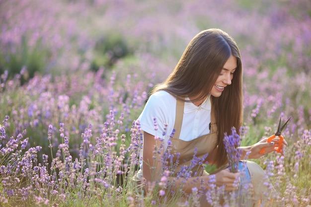 Ragazza allegra che raccoglie il raccolto di lavanda usando le forbici Foto Premium
