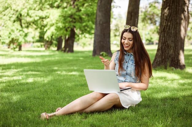 Ragazza allegra che comunica su internet o studia online usando il suo laptop mentre era seduto sul prato
