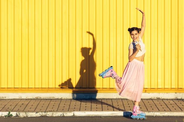 Una ragazza allegra mangia il gelato e rotola sui rulli in estate sullo sfondo di un muro giallo.
