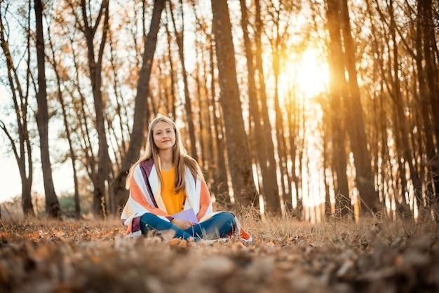 Ragazza allegra che si diverte nel parco autunnale leggendo libri godendosi la bellezza della natura