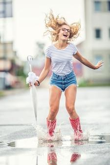 Ragazza allegra che salta con l'ombrello bianco in galosce rosse punteggiate. caldo giorno d'estate dopo la pioggia donna che salta e sguazza nella pozzanghera