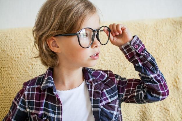 Ragazza allegra in una camicia a quadri e occhiali concetto di apprendimento online