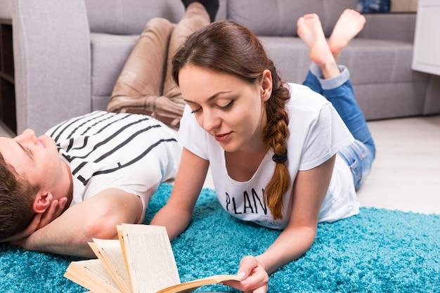 Ragazza allegra che legge un libro vicino al suo ragazzo sdraiato su un tappeto nel loro soggiorno in un'atmosfera rilassata