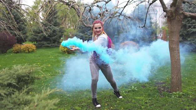 Una ragazza allegra in camicia e jeans con trecce arcobaleno luminose e trucco insolito. balla nascondendosi in un denso fumo artificiale blu