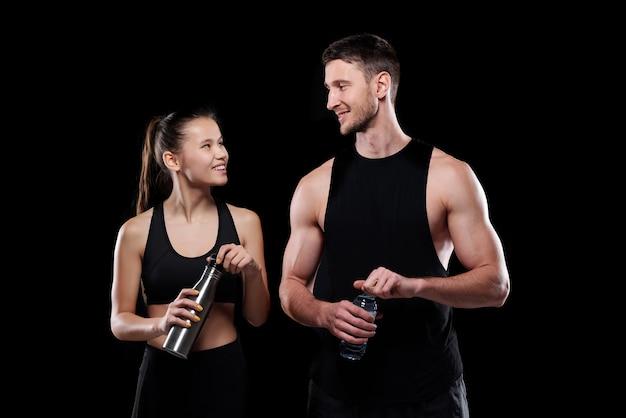 Ragazza allegra e sportivo con bottiglie d'acqua che si guardano con un sorriso mentre vanno a bere dopo l'allenamento