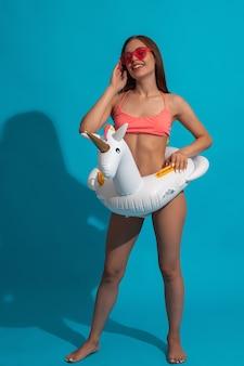 Ragazza allegra in costume da bagno con anello da bagno unicorno sulla parete blu