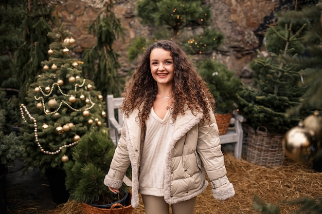 Una ragazza allegra cammina tra gli alberi e sorride, ha l'umore di capodanno