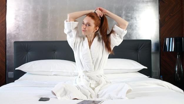 Ragazza allegra in camice con la compressa mentre rilassandosi sul letto di mattina