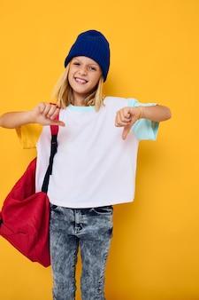 Ragazza allegra in un gesto di mano dello zaino della scuola della maglietta bianca