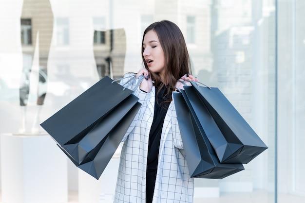 Ragazza allegra con borsa della spesa nera su sfondo vetrina. donna alla moda, venerdì nero.