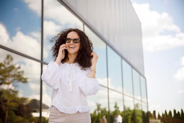 Ragazza allegra con i capelli ricci in occhiali da sole, parlando al cellulare, contro un edificio con sfondo della finestra.