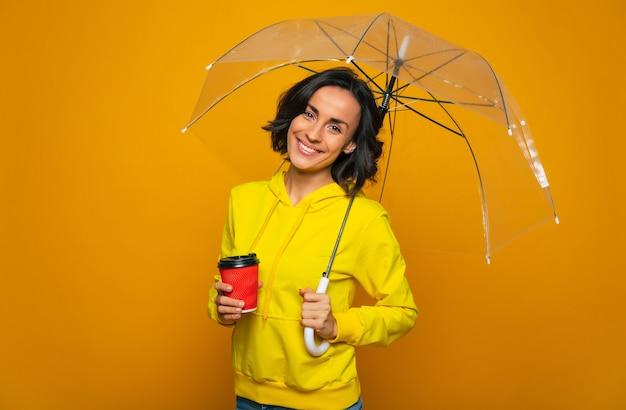 Ragazza allegra con un ampio sorriso sul viso sotto un ombrello trasparente, che tiene una tazza rossa nella mano destra vestita, con una felpa con cappuccio gialla.