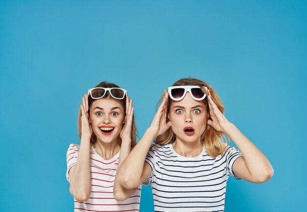 Ragazza allegra emozioni sorpresa occhiali da sole vista ritagliata sfondo blu comunicazione. foto di alta qualità