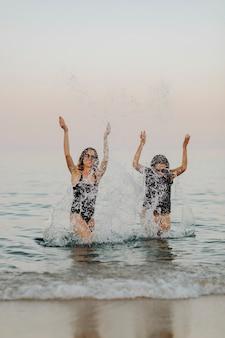 Ragazze allegre che spruzzano acqua in spiaggia