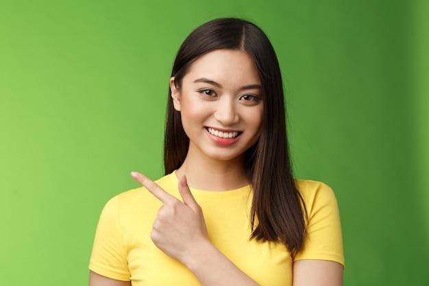 Allegra bella bruna asiatica che mostra un'eccellente opportunità promozionale, puntando il dito indice a sinistra, sorridendo felice, aiutando piacevolmente a introdurre il prodotto, in piedi sfondo verde. copia spazio