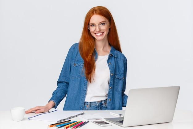 Allegra studentessa di bell'aspetto che realizza progetto artistico per classe di design all'università, in piedi vicino al tavolo con laptop, matite colorate e carta, disegno, raccogliendo ispirazione, muro bianco