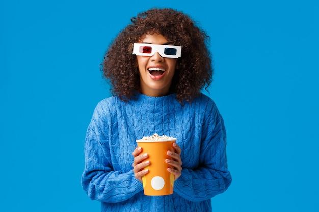 Allegra splendida donna afro-americana godendo di guardare film al cinema, ridendo e sorridendo eccitata con effetti 3d indossa occhiali