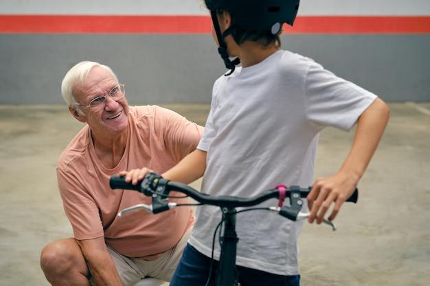 Nonno allegro con ragazzo senza volto in bicicletta