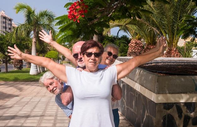 Allegro gruppo di amici anziani che si godono le vacanze - quattro pensionati in un parco pubblico con palme e piante in fiore - concetto di pensionamento attivo