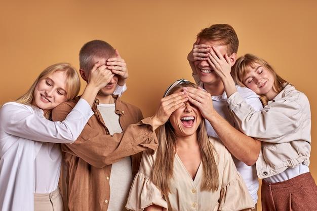 Allegro gruppo di giovani chiudendo gli occhi l'un l'altro divertendosi isolato su sfondo marrone