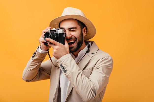 Il ragazzo allegro in abito beige scatta foto sulla fotocamera