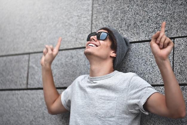 Ragazzo allegro vestito con occhiali da sole e cappello in maglietta grigia allo spettacolo di strada grande vendita o bella offerta