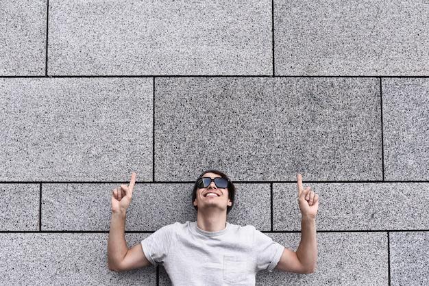 Il ragazzo allegro vestito con gli occhiali da sole e il cappello grigi della maglietta alla via mostra una grande vendita
