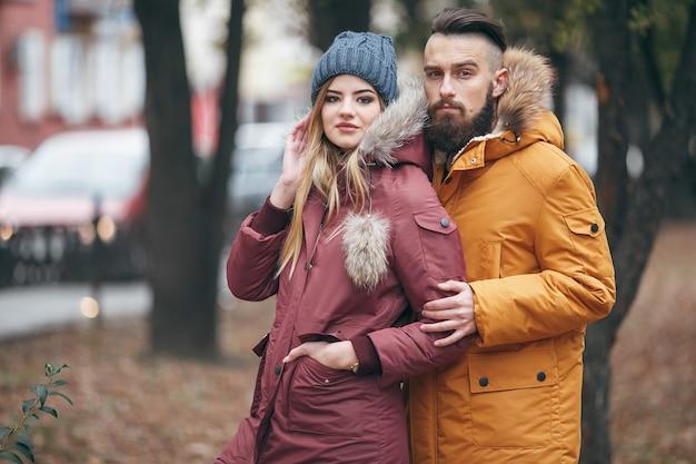 Un ragazzo allegro e una ragazza stanno camminando nel parco d'autunno