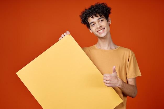 Ragazzo allegro con poster di capelli ricci gialli nella pubblicità di studio di mani
