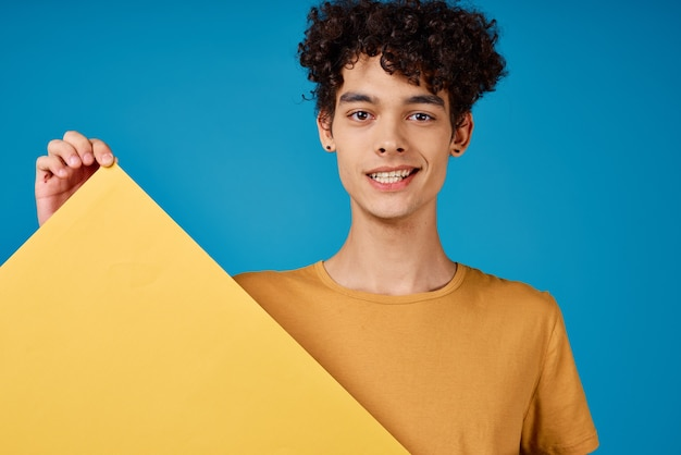 Ragazzo allegro con capelli ricci giallo poster mockup sfondo blu