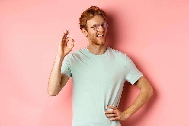 Ragazzo allegro con i capelli rossi e la barba con gli occhiali che mostra segno ok in approvazione e strizza l'occhio sorridendo...