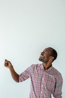 Allegro bell'uomo afroamericano che tiene un ombrello contro il muro bianco