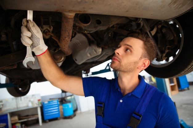 Specialista di riparazione auto allegro, bello e sicuro di sé in riparazioni di tute e sostituisce parti vecchie con nuove in un'auto su un ascensore in servizio Foto Premium