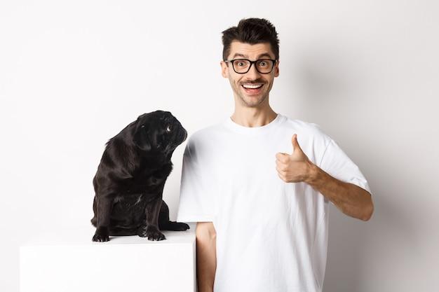 Ragazzo bello allegro che sta vicino al carlino nero sveglio e che mostra il pollice in su. il proprietario dell'animale domestico approva e consiglia il prodotto per cani, bianco.