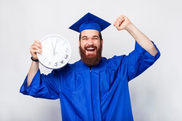 Uomo bello allegro in scapolo blu che tiene orologio bianco e festeggia and