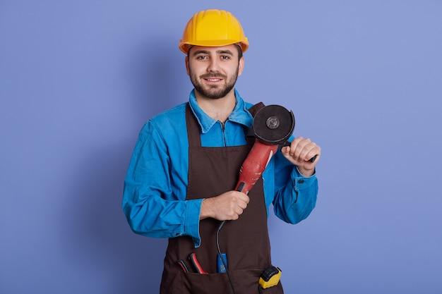 Costruttore positivo bello allegro guardando direttamente la fotocamera e sorridendo sinceramente, tenendo la smerigliatrice in mano, indossando il grembiule