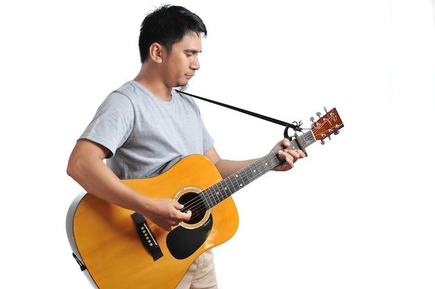 Allegro bel giovane che suona la chitarra isolato su sfondo bianco