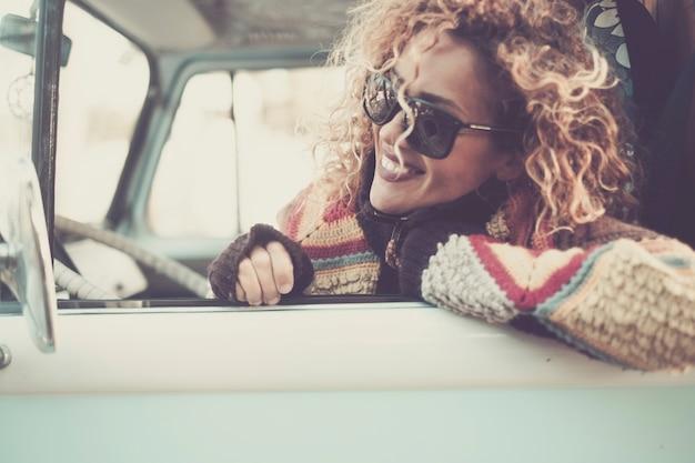 Allegra felice bella giovane donna caucasica che guarda e sorride fuori dalla finestra dal vecchio autobus vintage con occhiali da sole