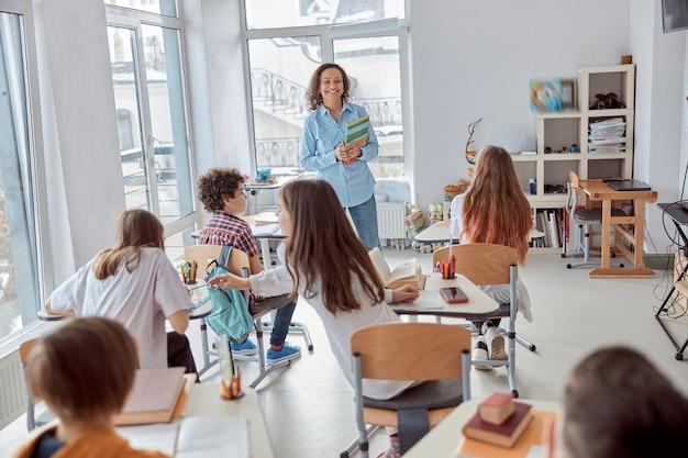 Bambini allegri e felici che si siedono allo scrittorio mentre l'insegnante che parla nell'aula della scuola.