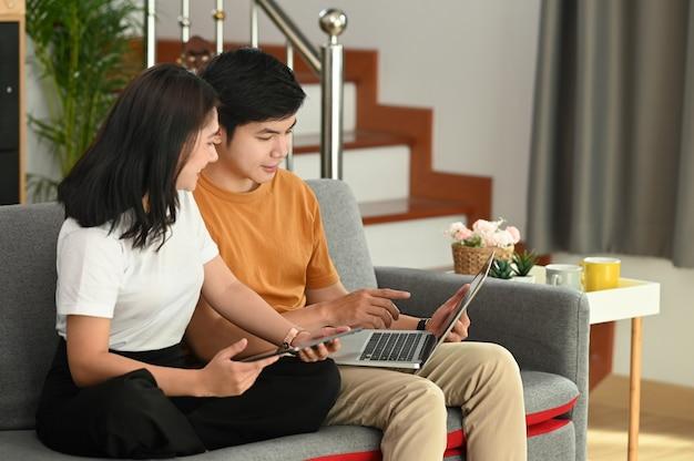 Coppie felici allegre stanno utilizzando il computer portatile per guardare video divertenti sul divano